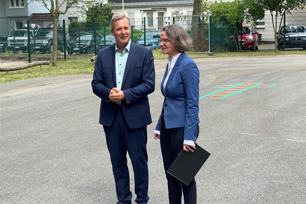Bürgermeister Jürgen Kleine-Frauns (l.) hat den Förderbescheid von Ministerin Ina Scharrenbach auf dem Schulhof der Viktoriaschule entgegengenommen. | Foto: Stadt Lünen.